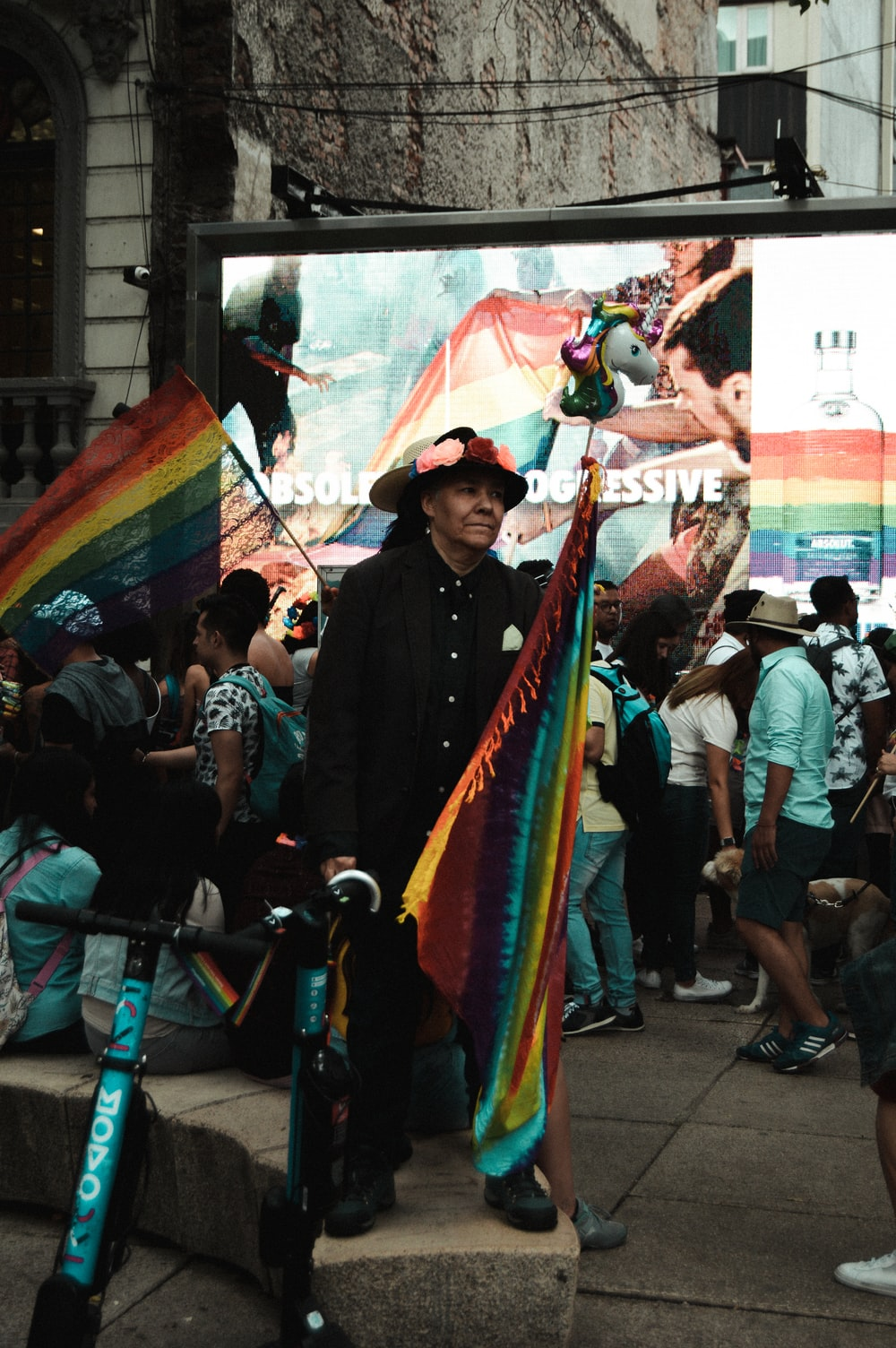 man standing and holding multicolored flag surrounded with people near building