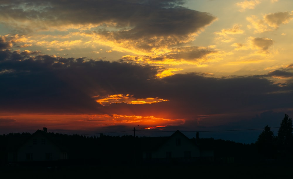 silhouette of mountain under orange and yellow skies