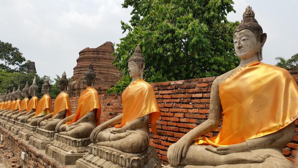 orange and brown buddha statue lot during daytime
