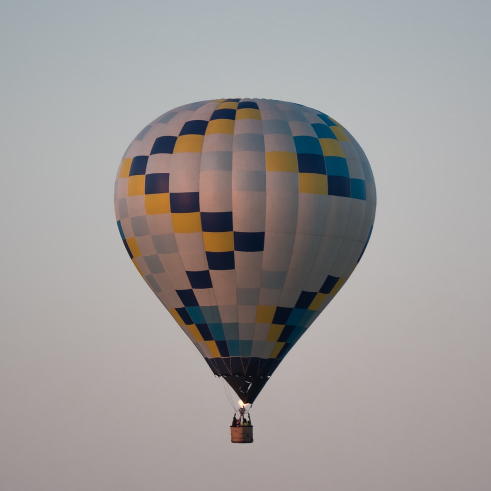blue, white, and yellow air balloon in flight