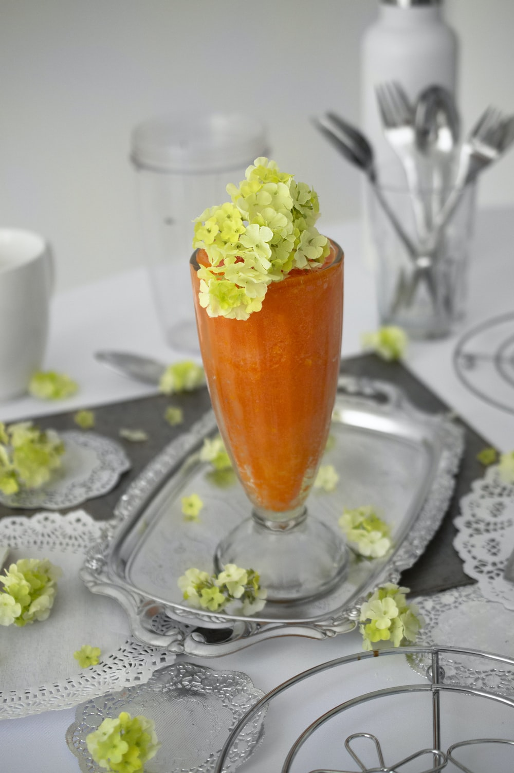 orange shake in footed drinking glass with petaled flowers