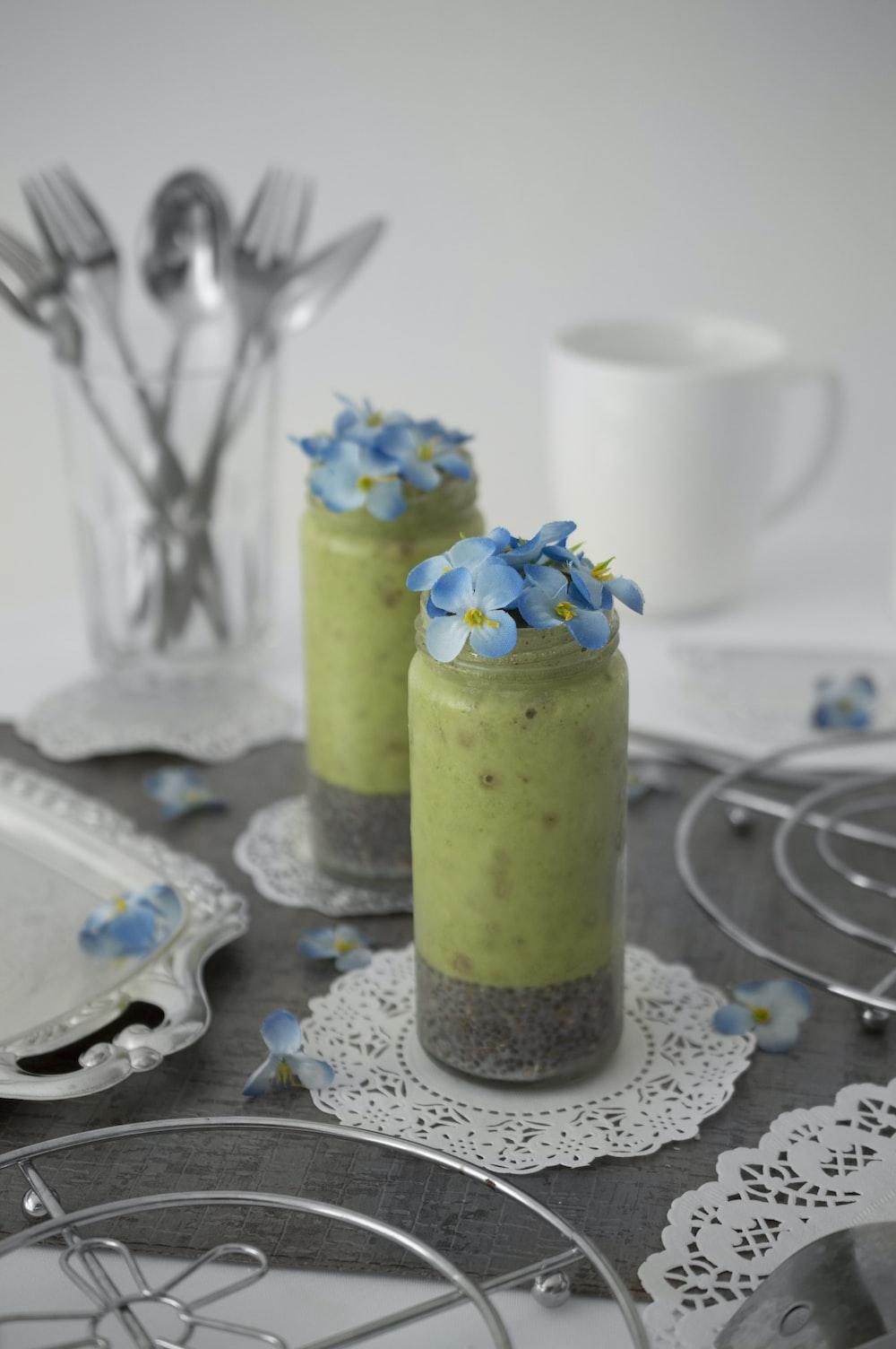 blue petaled flower in glass on table beside plates
