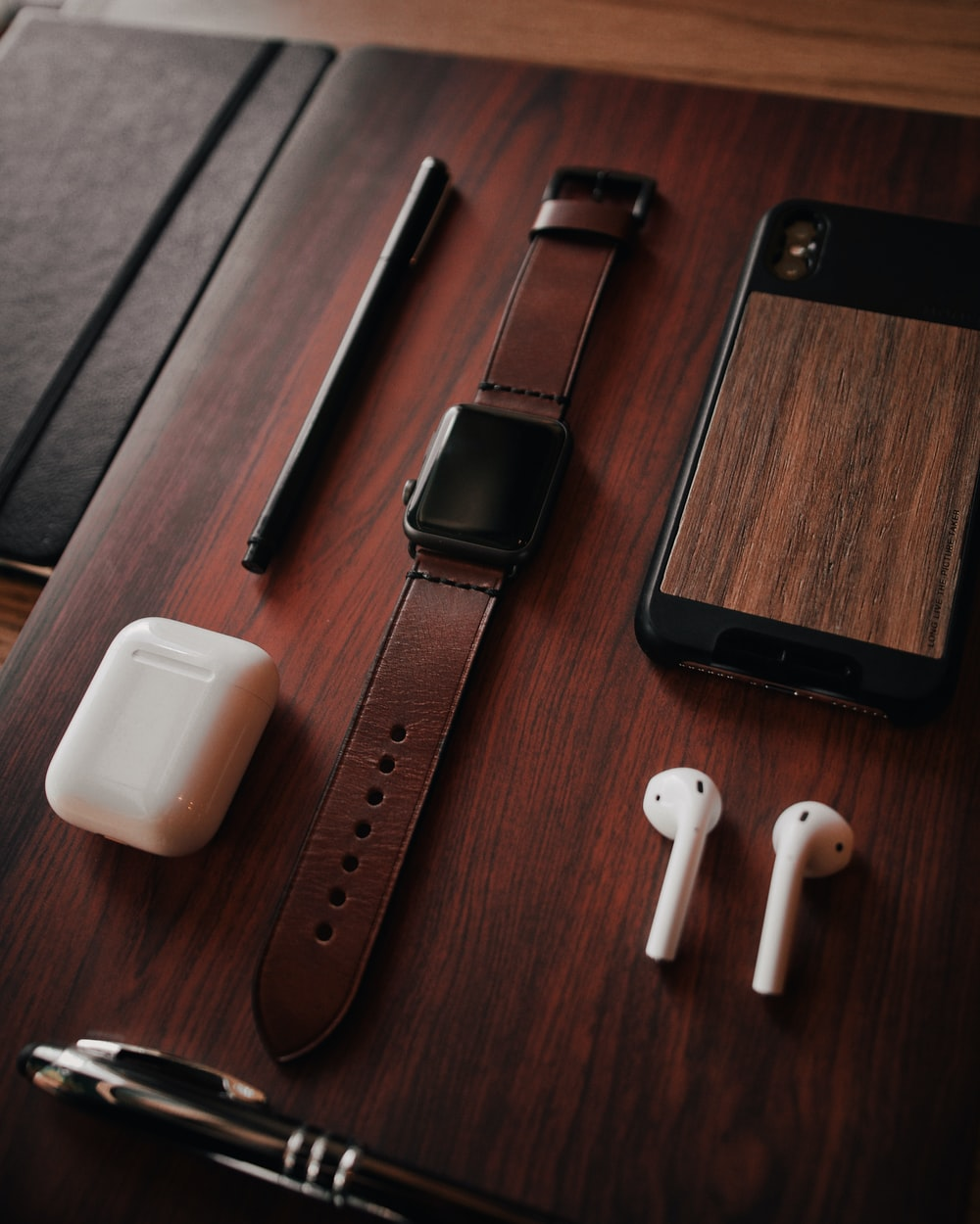black aluminum Apple Watch with brown leather band, Apple AirPods with case, black pen, and brown and black case on brown wooden surface