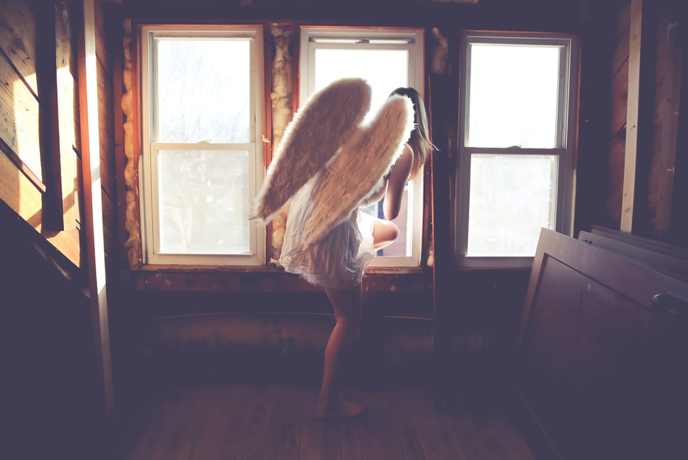 woman in white dress with wings about to jump on window