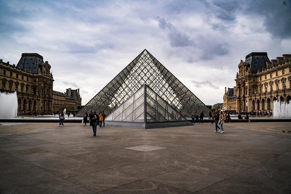people walking near triangle glass building