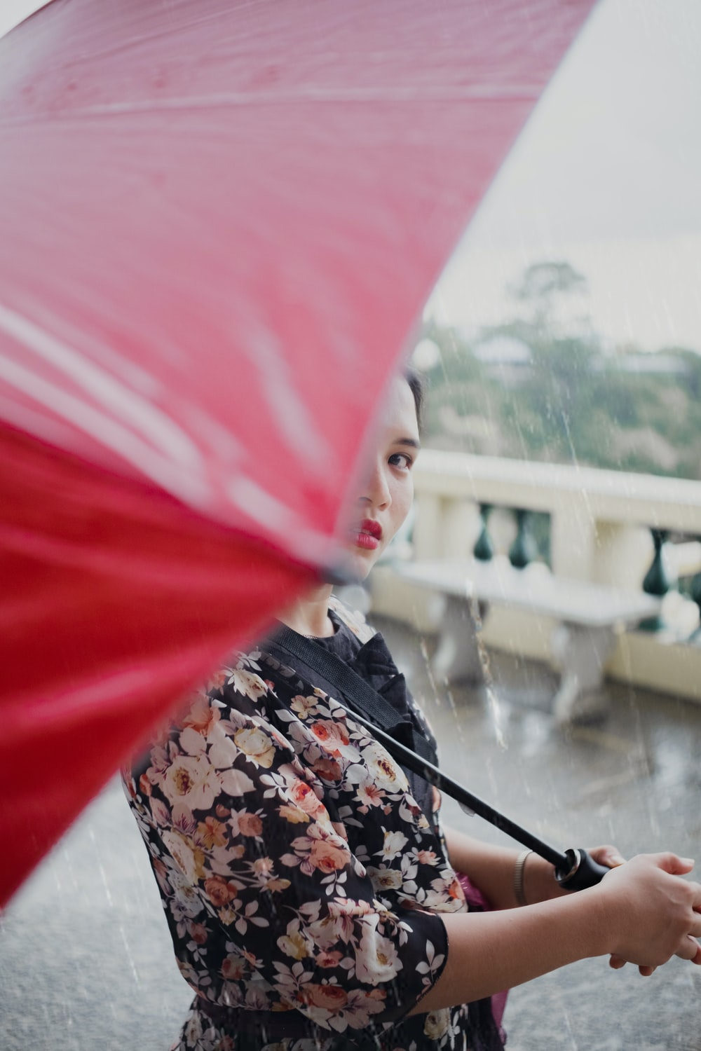 woman wearing floral top under red umbrella