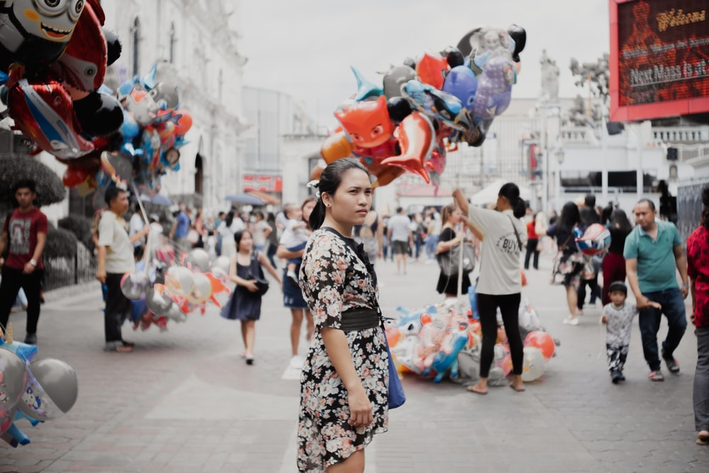 woman wearing multicolored floral dress standing in the middle of road during daytime