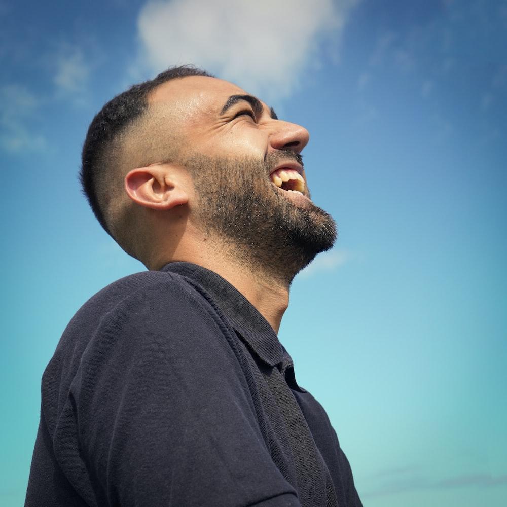 smiling man wearing black collared top