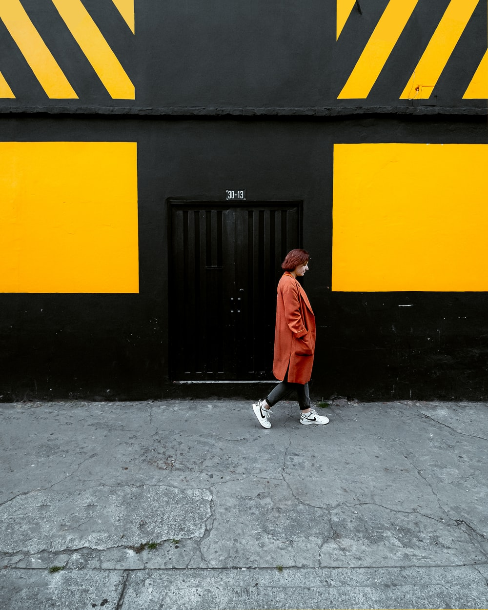 woman walking beside black and yellow building during daytime