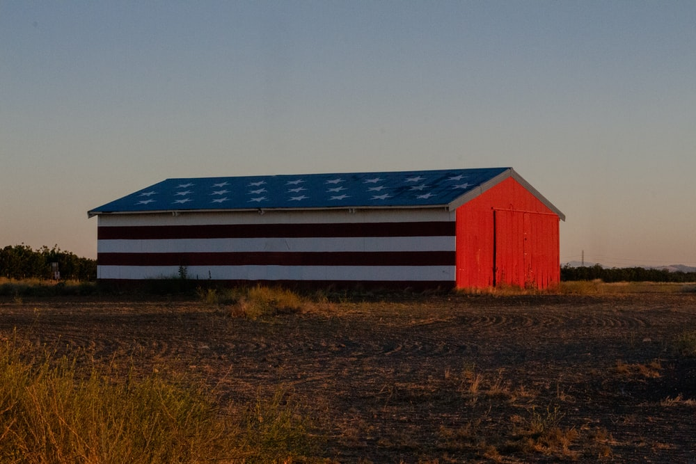 red and white barn during golden hour