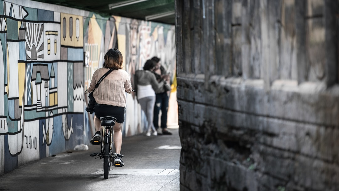Woman was riding a bicycle in the street with painted wall nearby as a street art.