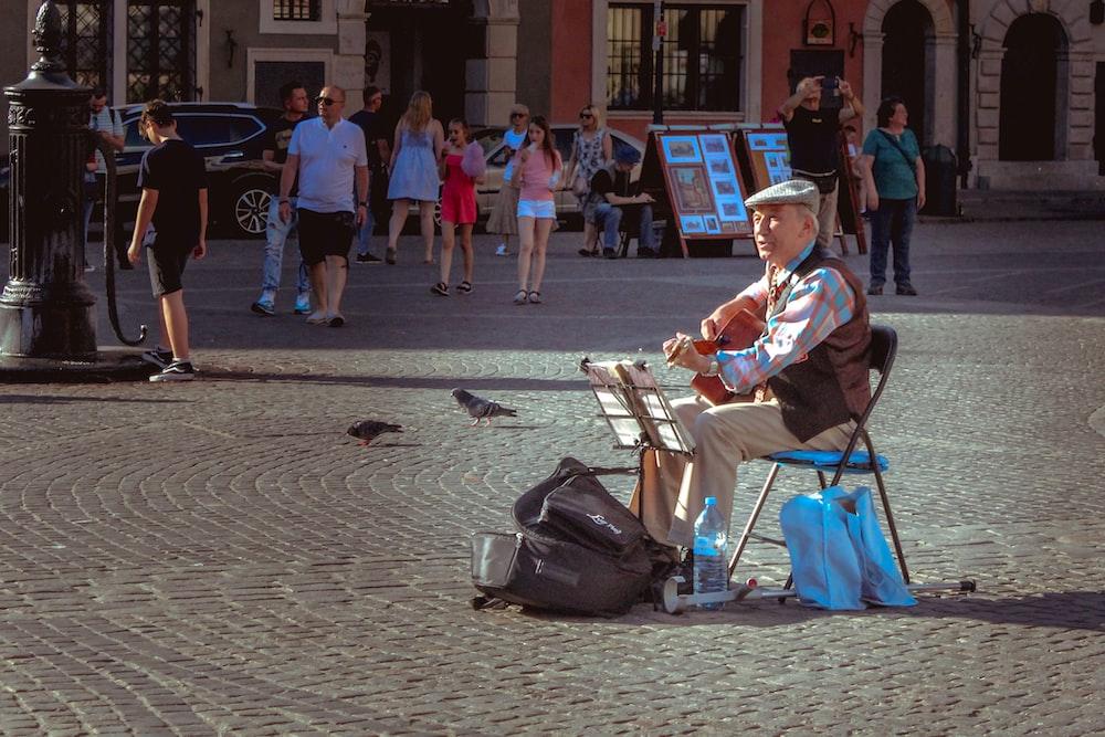 man sitting on folding chair playing guitar