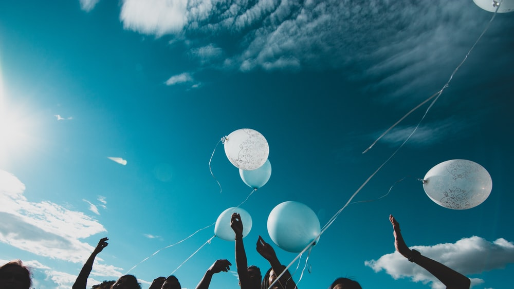 low angle photo of people holding balloons