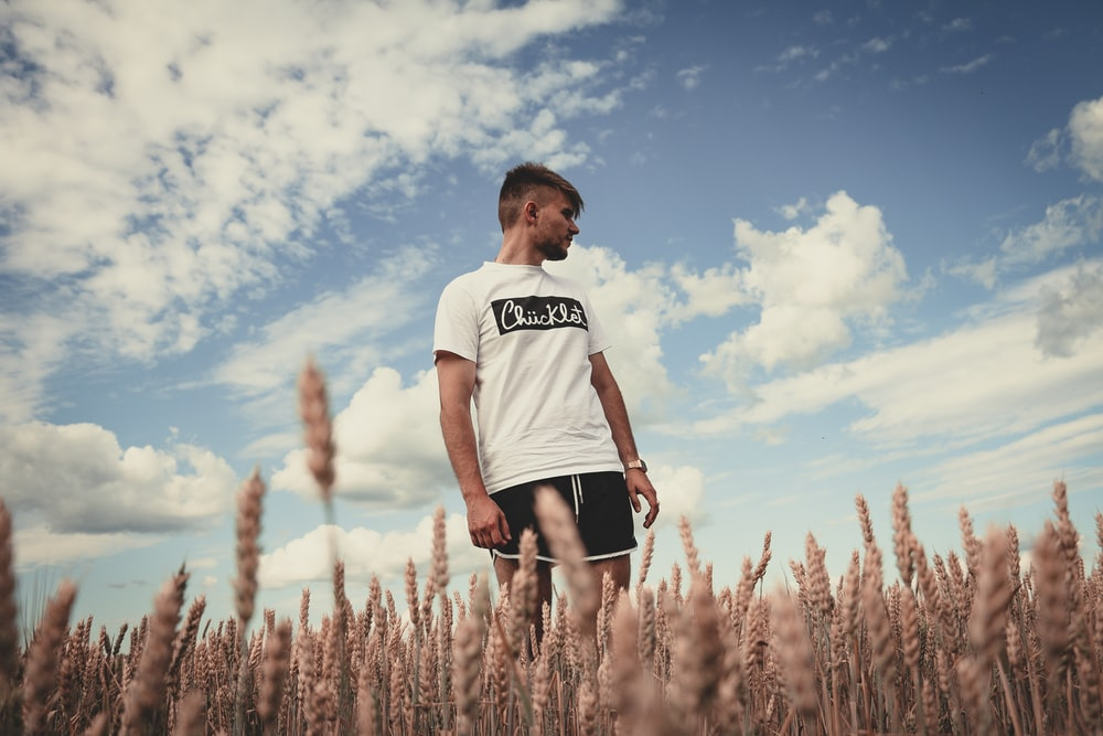 man standing in whey field