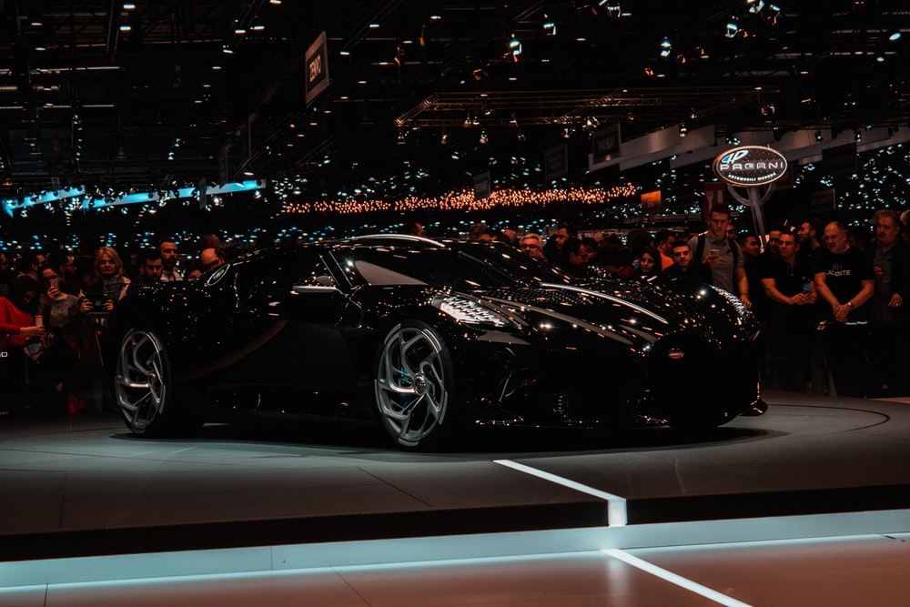 black sports car parked beside crowd