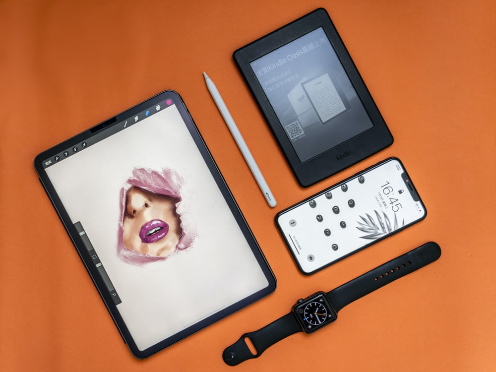 flat lay photography of two tablet computers, iPhone, and Apple watch