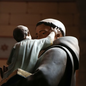 religious man carrying child statue