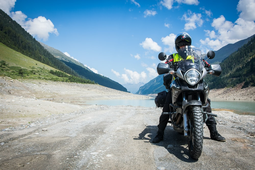 man riding motorcycle beside body of water