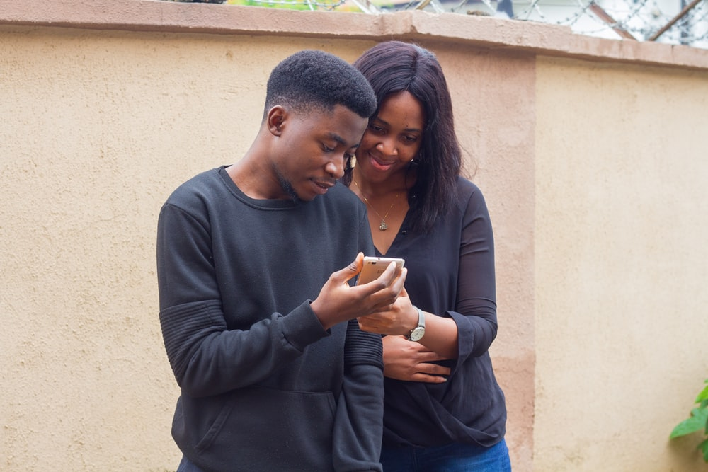 man and a woman looking at a smartphone