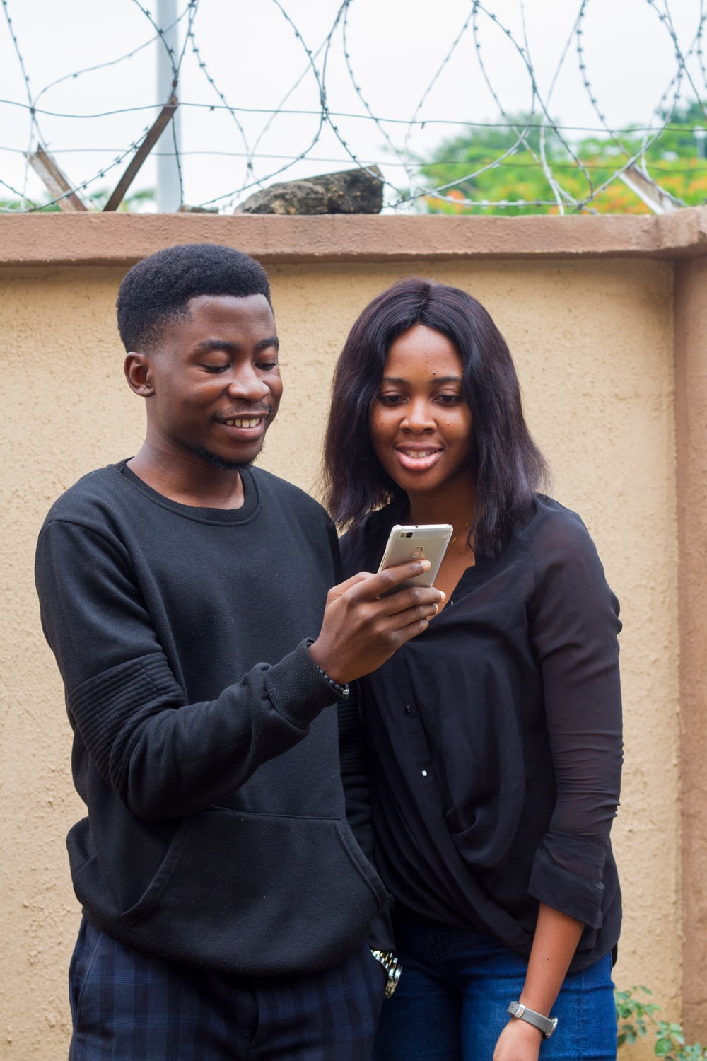 man holding smartphone beside smiling woman standing beside wall