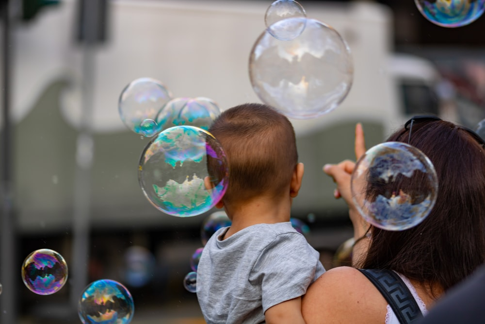 woman carrying baby near bubbles