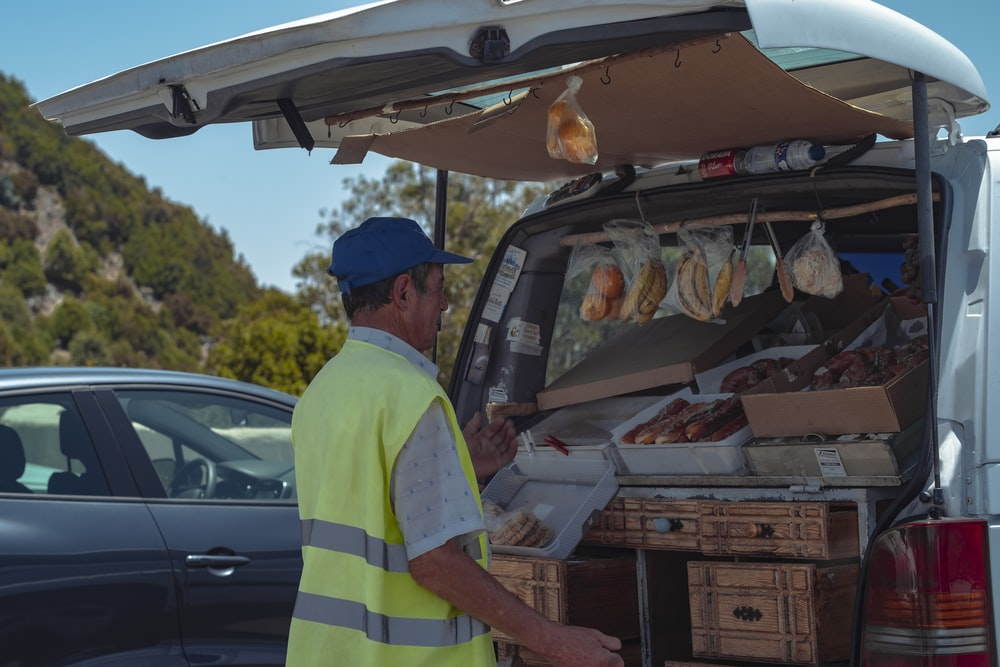 man selling food using a vehicle trunk