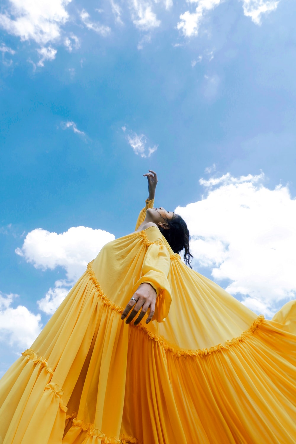 woman wearing yellow long-sleeved dress under white clouds and blue sky during daytime