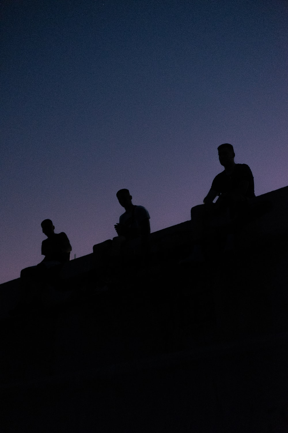 silhouette view of three men sitting on the roof