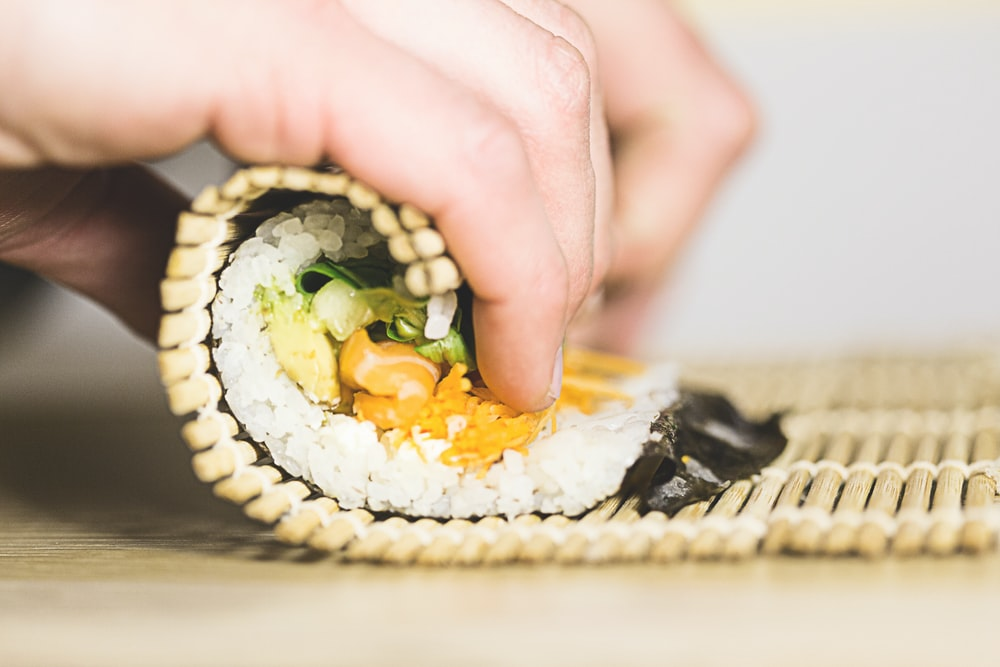 person rolling sushi
