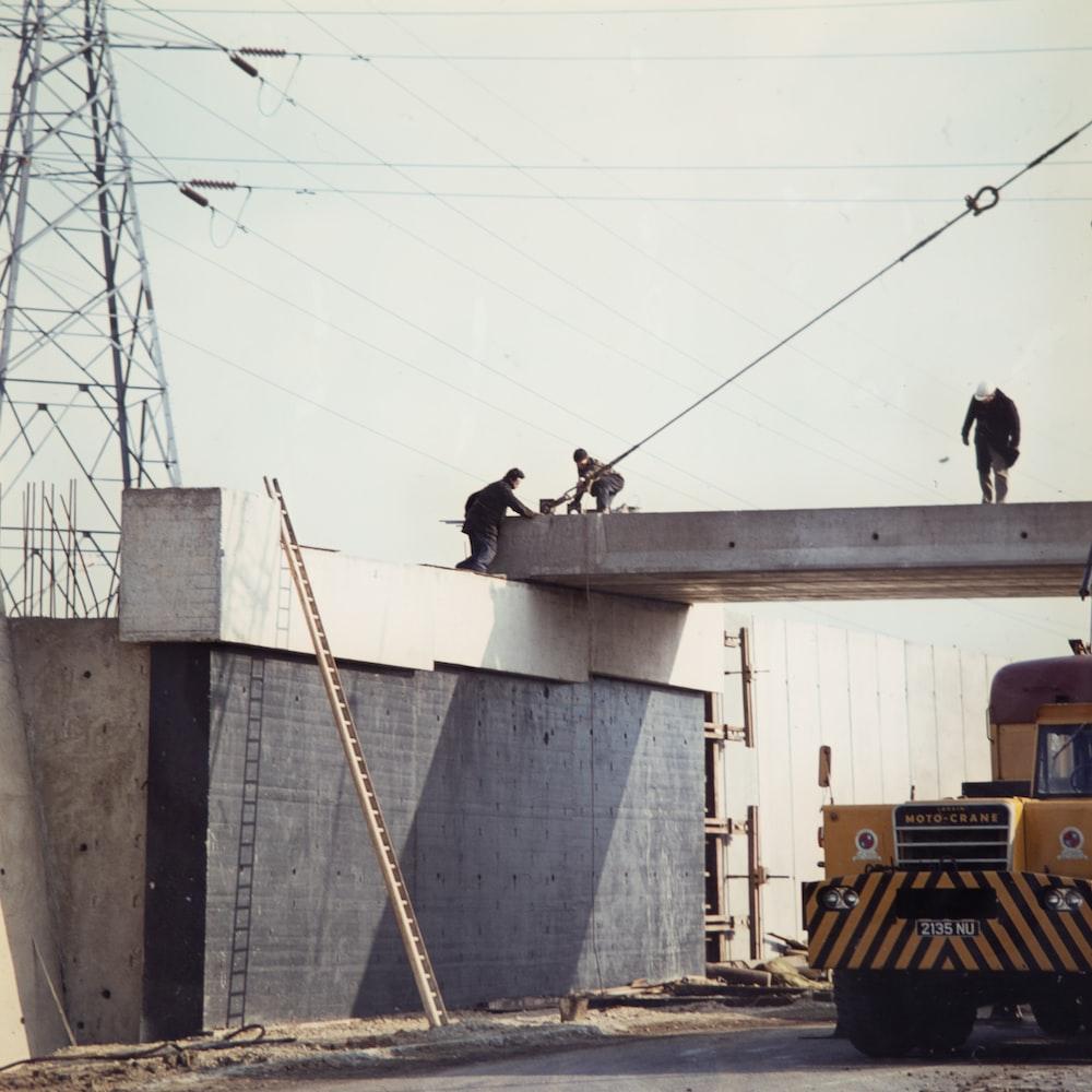 three people working bridge during daytime