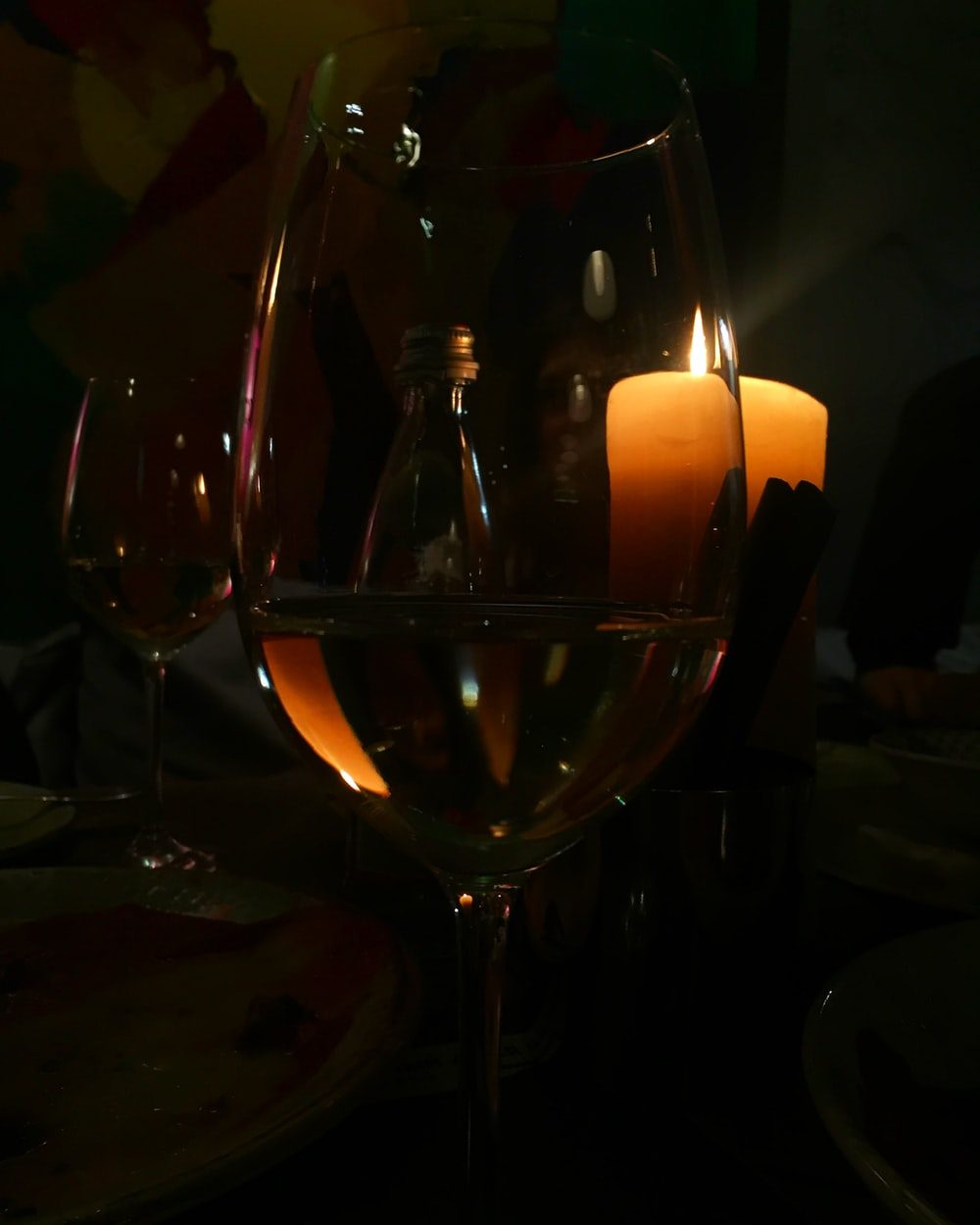 white wine in wine glass near lighted yellow pillar candles