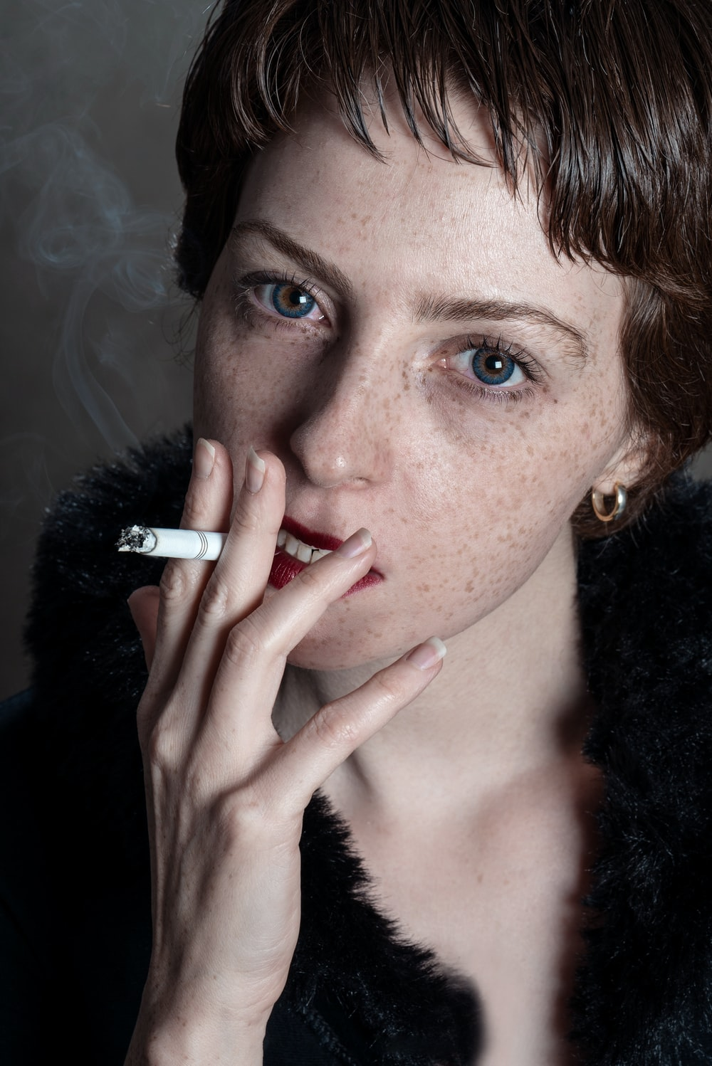 woman wearing black fur coat smoking