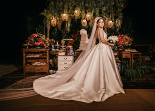 bride holding flower standing near furniture painting