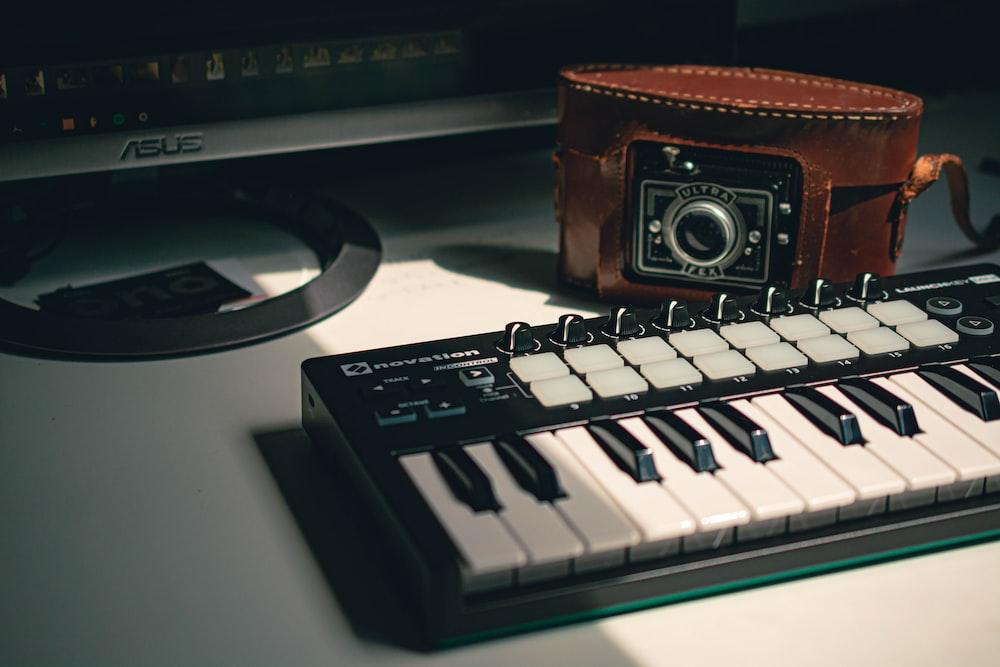 black electronic keyboard near black camera