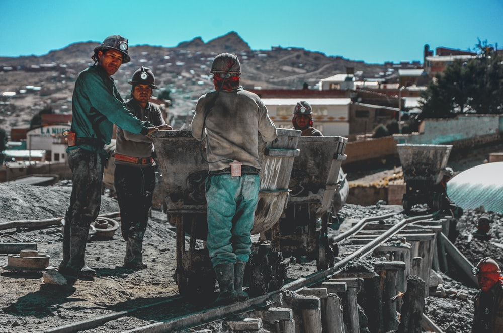 construction workers standing near wheelbarrows near mountain