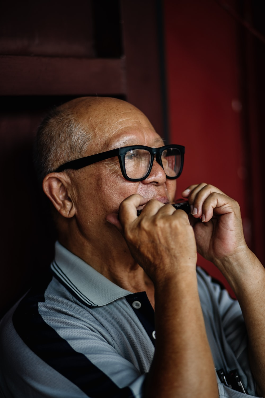man in grey and black polo shirt using harmonica