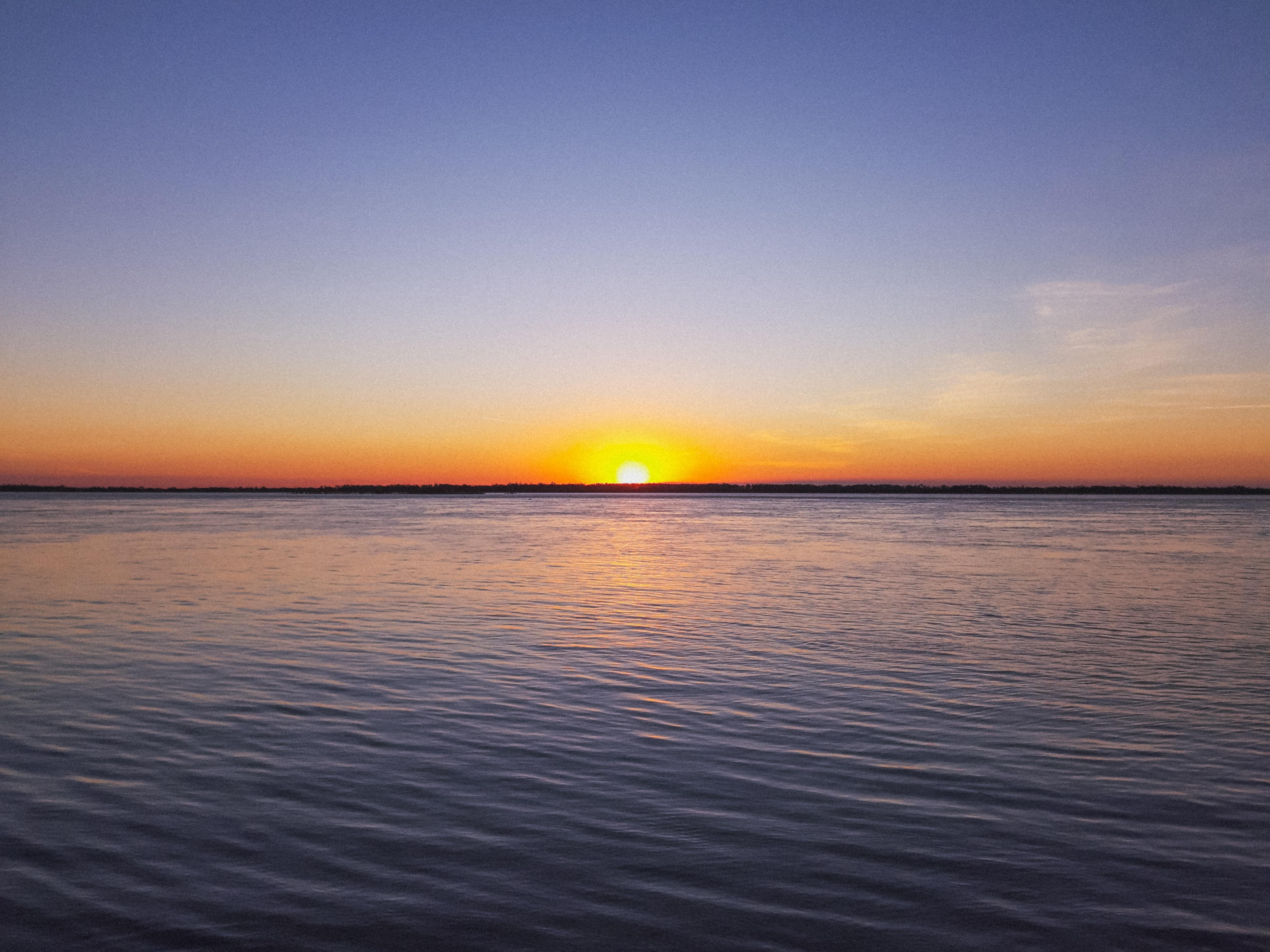 blue calm sea during sunrise