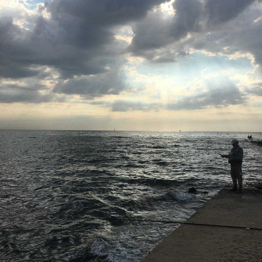 man standing in pier near water