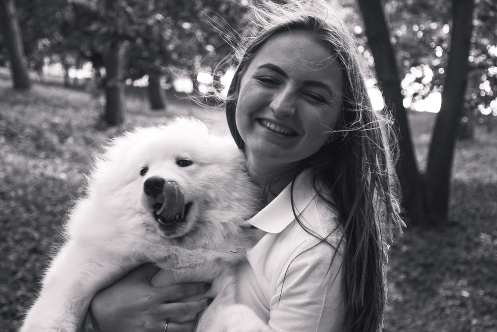 grayscale photography of woman carrying dog