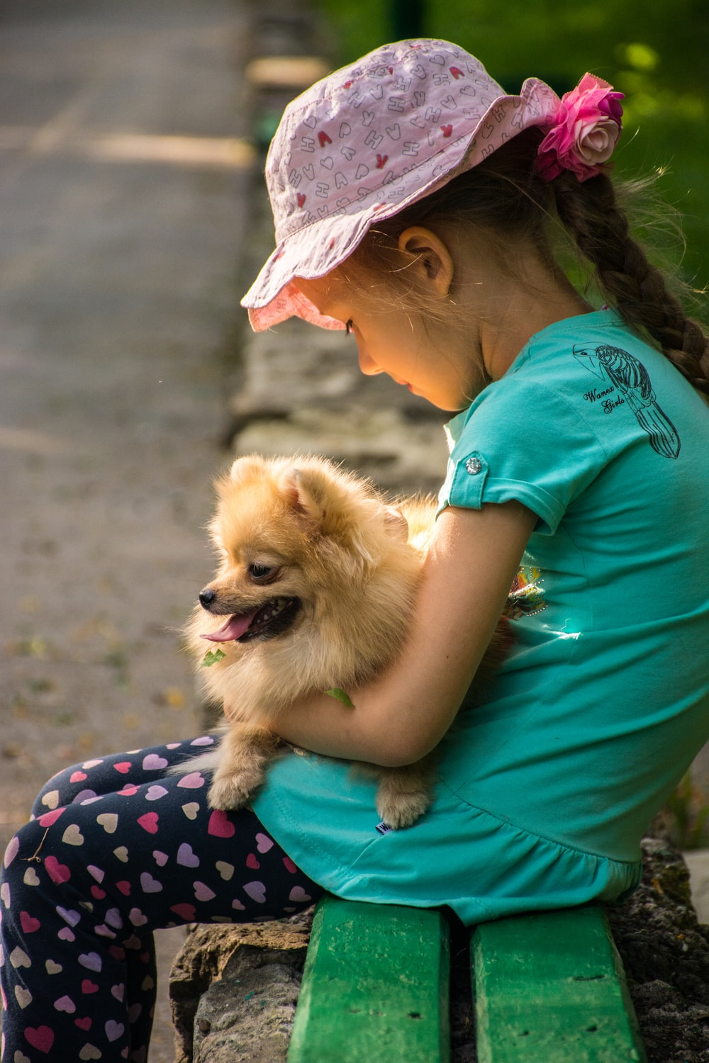 girl sitting and carrying brown Pomeranian puppy