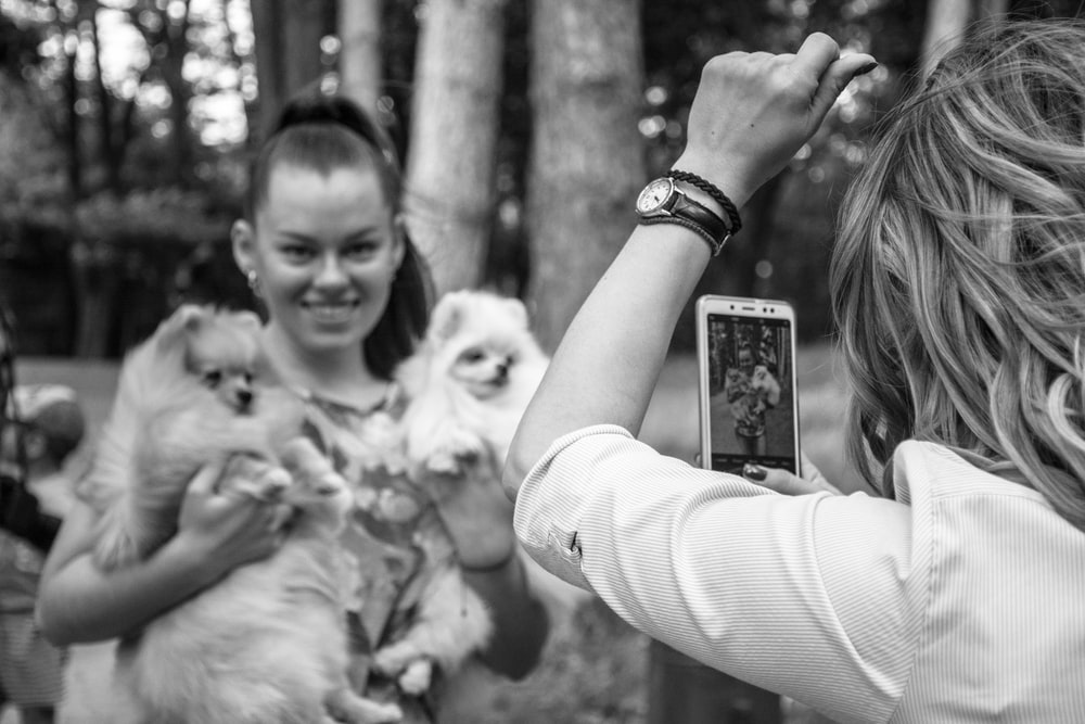 grayscale photo of woman holding phone taking picture of woman carrying two dogs