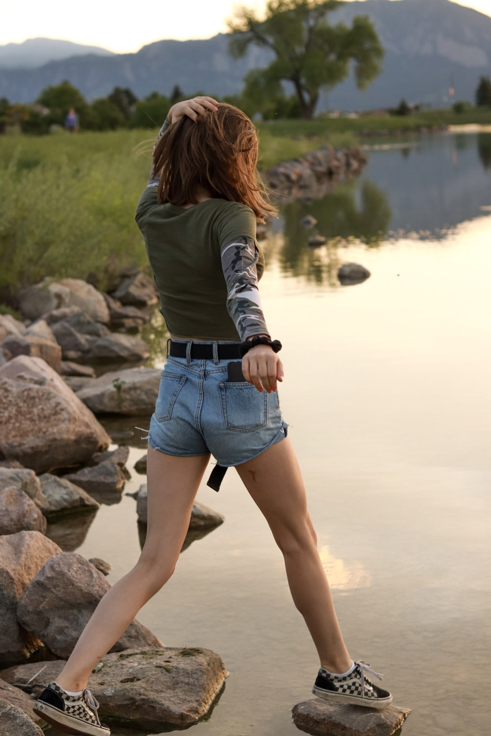 woman wearing gray sweater and blue denim short shorts