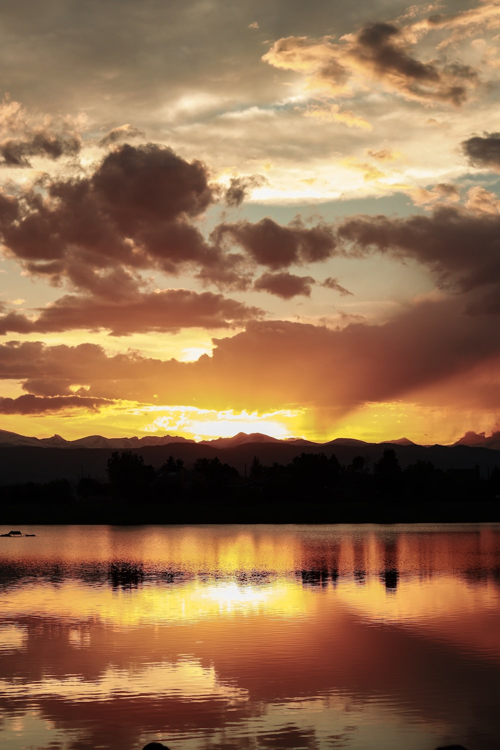 silhouette of mountain and trees near lake under orange sky and clouds