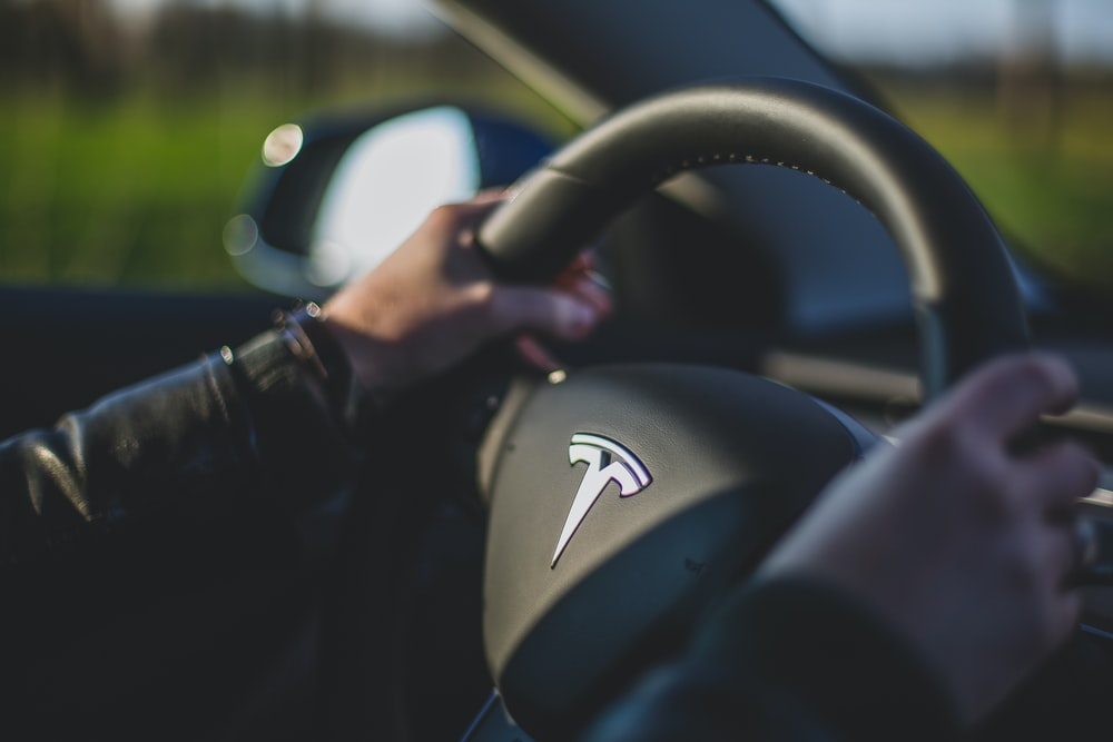 person holding black Tesla steering wheel