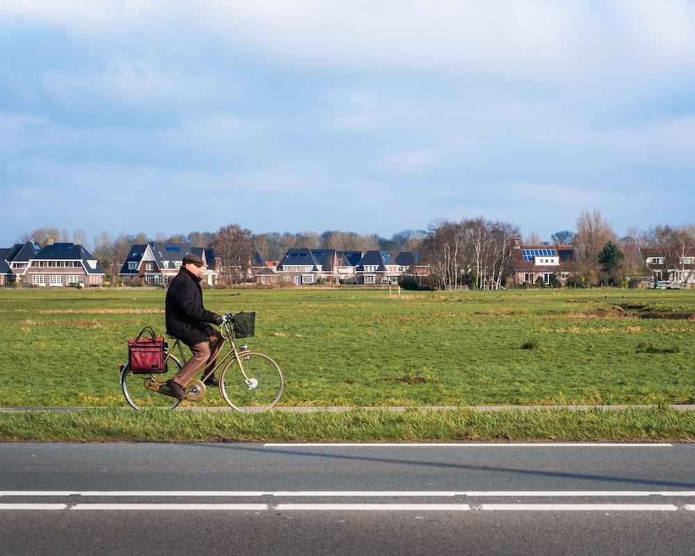man biking near green field under blue and white skies