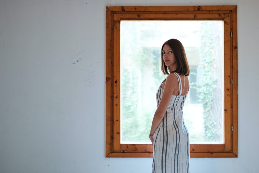 woman wearing white and blue pinstriped maxi dress i front of window