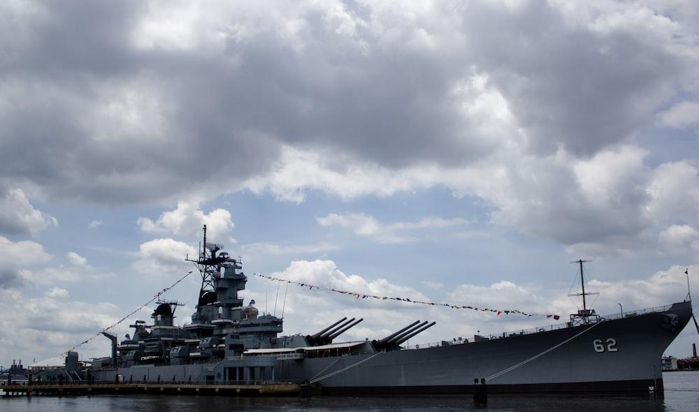grey and black boat under grey clouds