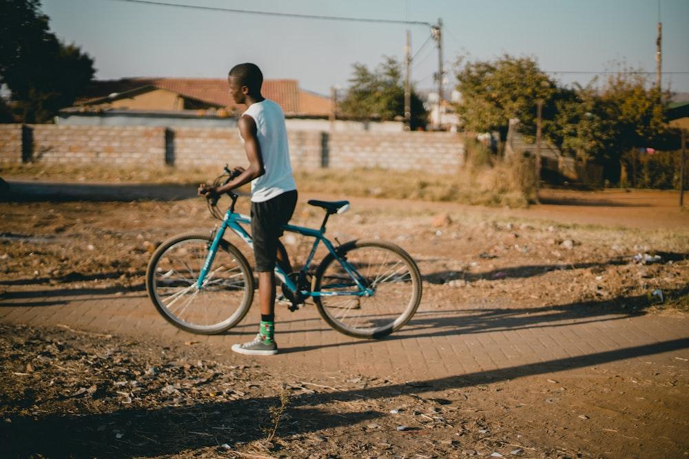 man standing beside rigid bicycle
