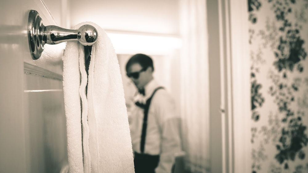 grayscale photography of towel near man wearing long-sleeved shirt