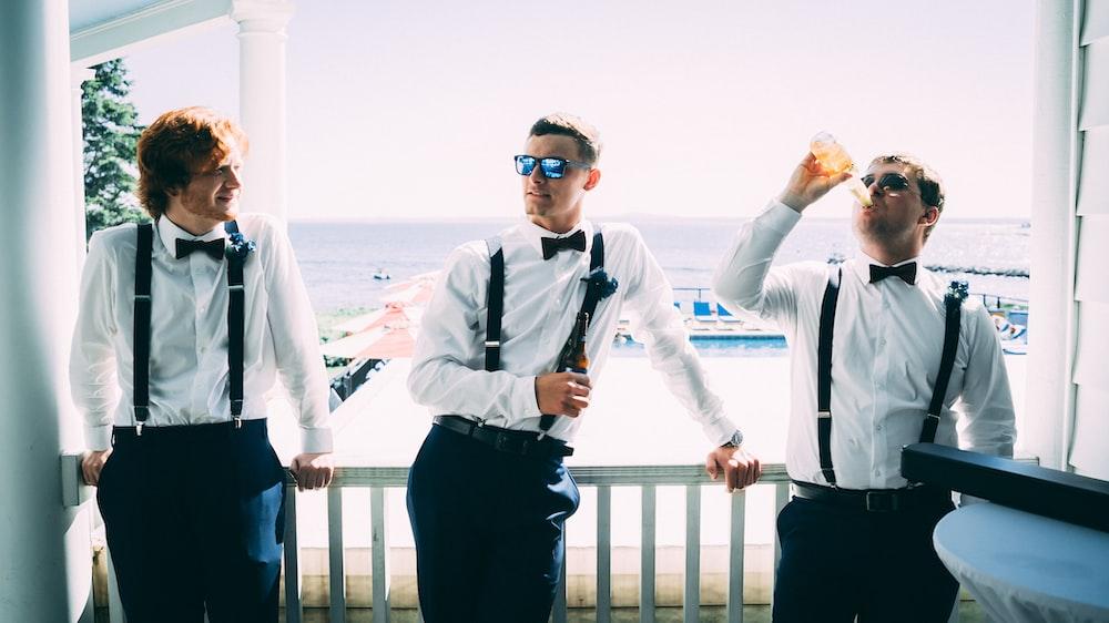 three men wearing white dress shirt and black bow tie